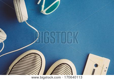 Audio Cassette And Headphones On A Blue Background. Music Concept