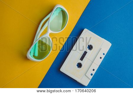 White Sunglasses And Audio Tape On A Blue Yellow Background. Rest Concepts