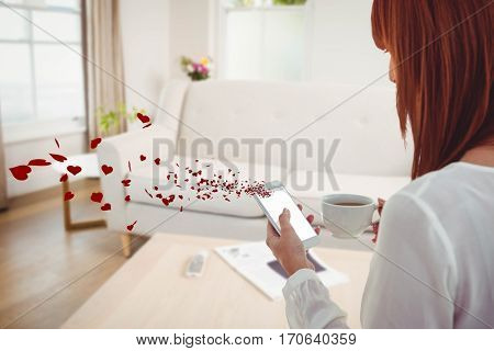 Conceptual image woman texting on mobile phone with digitally generated red hearts in living room