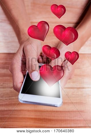 Composite image of hand using mobile phone with digitally generated red heart