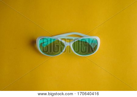 White Sunglasses On A Yellow Background. Rest Concepts