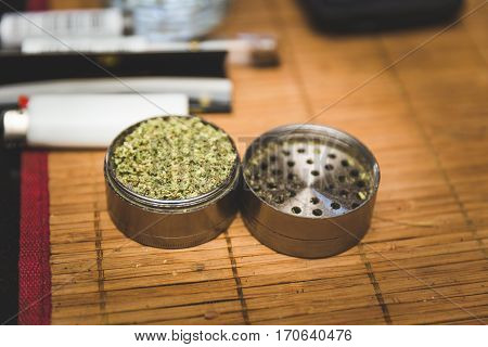 Steel or metal grinder full of freshly ground cannibus flower. Related smoking accessories nearby.