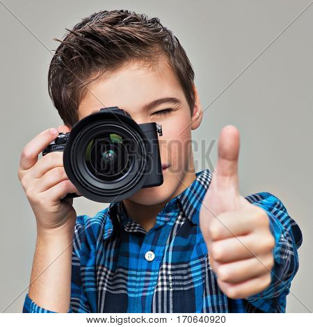 Boy with photo camera taking pictures. Teenager  boy  with photo camera shows the thumb up