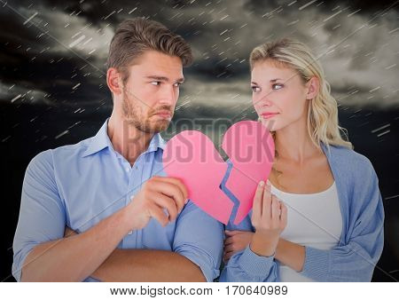 Composite image of depressed couple holding broken heart with storm clouds in background