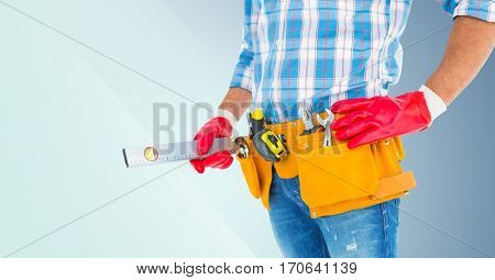 Mid section of handyman with tool belt and spirit level against grey background