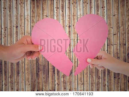 Close-up of hands of couple holding broken heart against wooden background