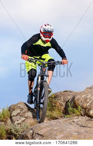 Professional Cyclist Riding the Bike on the Top of the Rock. Extreme Sport Concept.