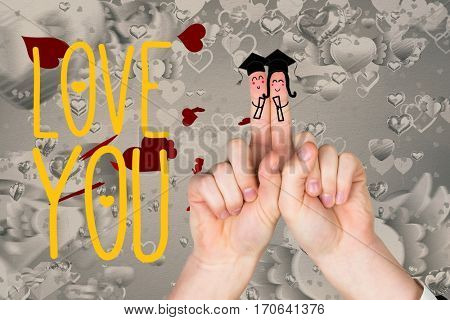 Smiling finger couple in mortarboard, love you message and hearts against white background