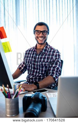 Portrait of hipster photographer smiling at camera while sitting at desk in studio