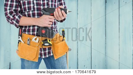 Mid section of handyman with tool belt and drill machine against wooden background