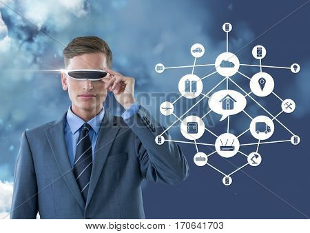 Business man wearing vr glasses standing next to digitally generated connecting icons against sky