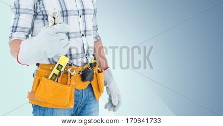 Mid section of handyman with tool belt and wrench against blue background