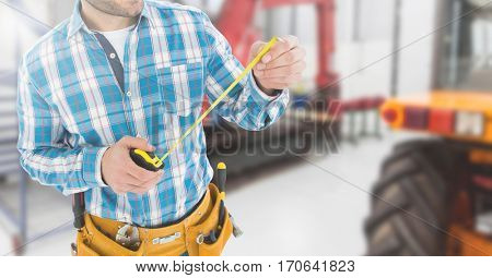 Mid section of handyman with tool belt and measuring tape in workshop