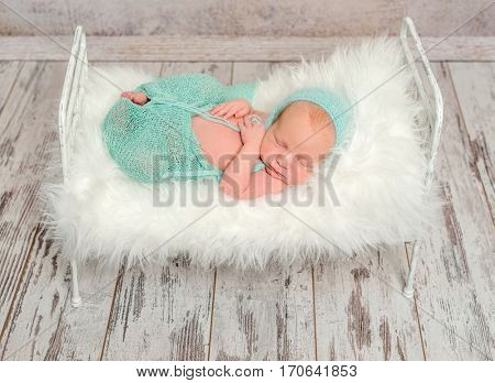 lovely wrapped newborn sleeping on cot with white soft blanket and toy