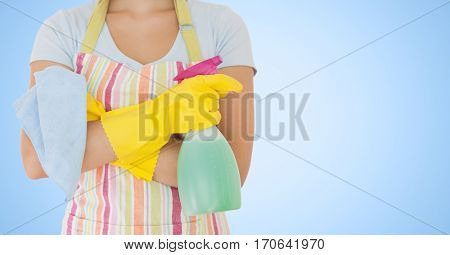 Mid section of female cleaner with spray bottle against blue background