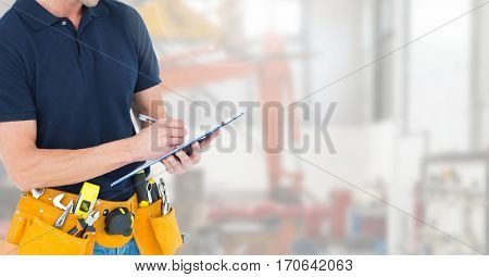 Mid section of construction man with tool belt writing on clipboard