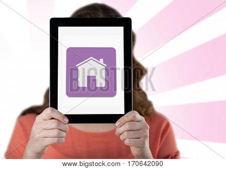 Woman holding digital tablet with home icon in front her face against white pink background