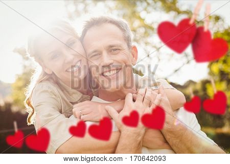 Composite image of red hanging heart and happy couple embracing each other in park
