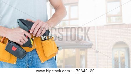 Mid-section of handy man with tool belt and drill standing against a building