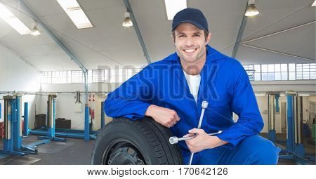 Smiling mechanic leaning on the tire in garage
