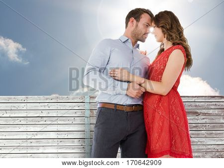Romantic couple rubbing nose each other with a wooden wall and sky as background