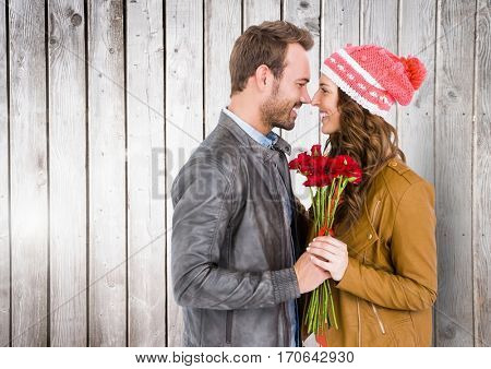 Romantic couple holding bunch of flowers rubbing nose against wooden background