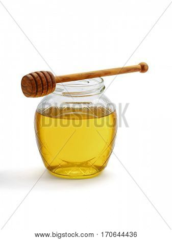 Glass jar full of honey wooden dipper