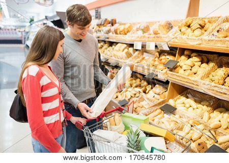 Couple buying French baguette on a grocery