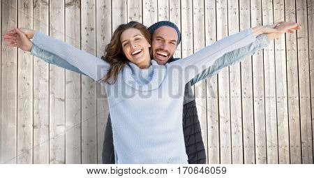 Portrait of happy couple standing with arms outstretched against wooden background