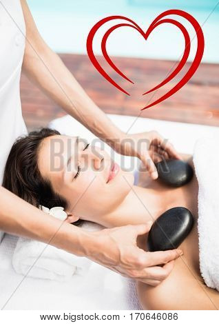 Composite image of masseur giving stone massage to woman at spa