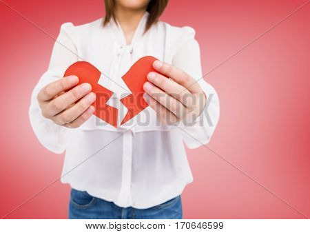 Mid-section of a woman holding a broken heart against pink background