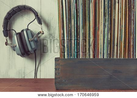 Old vinyl records in a wooden box and headphones