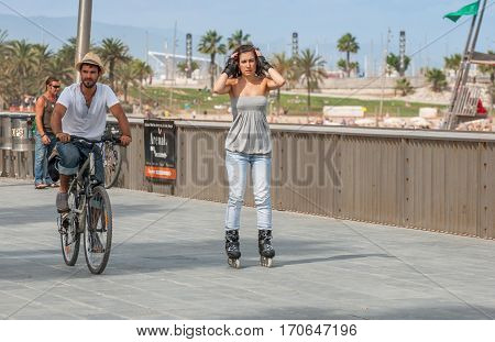 Boy On Bicycle And Girl On Rollerblade At Barceloneta Street