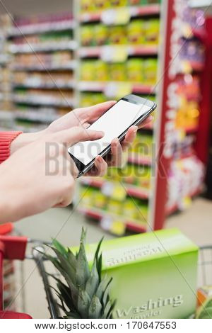 Focus on foreground of woman touching her mobile phone on a grocery