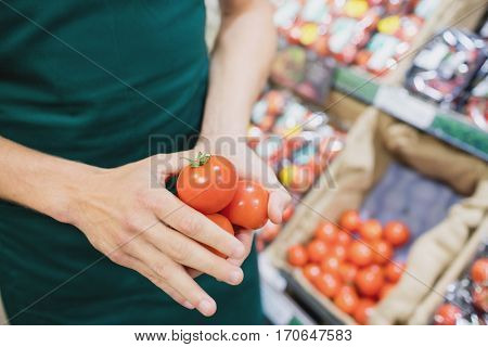 Focus on foreground of man grocer holding tomatoes on a grocery