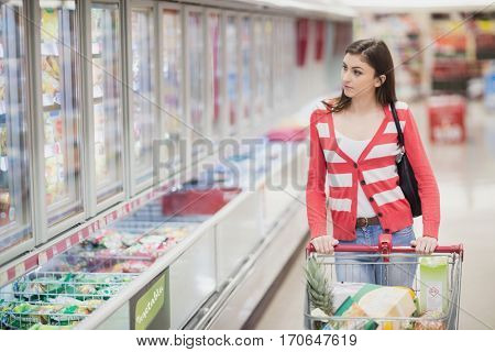 Woman walking with her trolley on a grocery