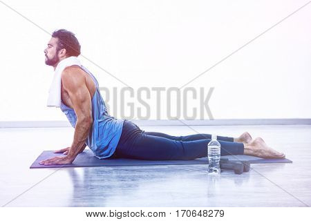 Man doing cobra pose on exercise mat in fitness studio
