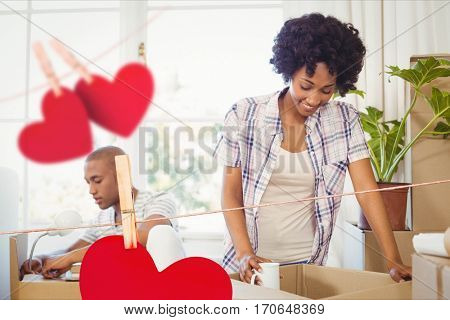 Composite image of red hanging hearts and couple unpacking cardboard boxes