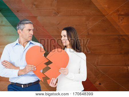 Sad mature couple holding broken heart against wooden background