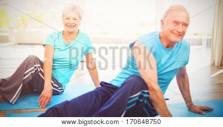 Happy senior couple doing yoga on exercise mat at home