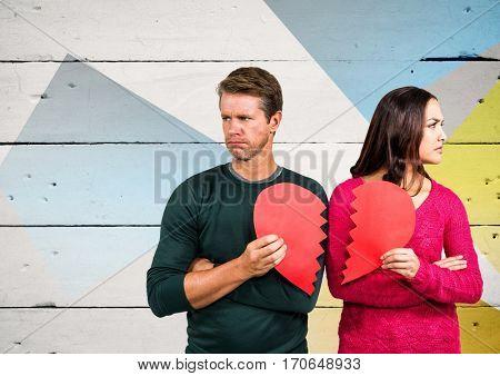Sad couple holding broken heart against wooden background