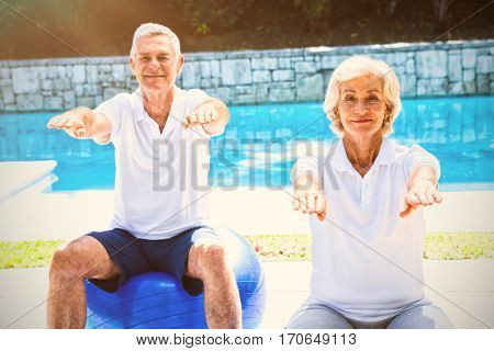 Portrait of smiling senior couple doing aerobics at poolside