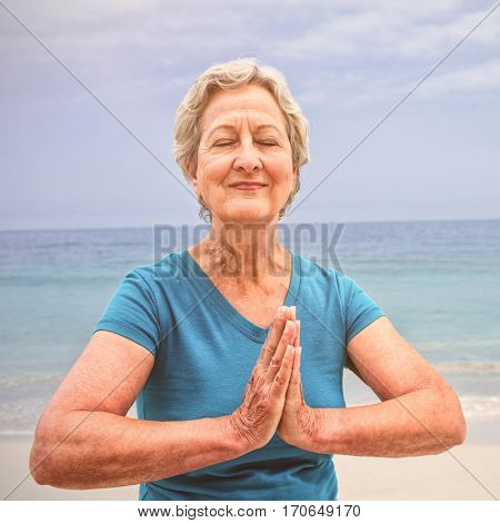 Happy senior woman in lotus position on the beach