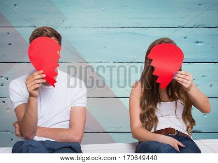 Couple hiding their face behind broken heart against wooden background