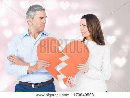 Mature couple holding a broken heart against digitally generated background