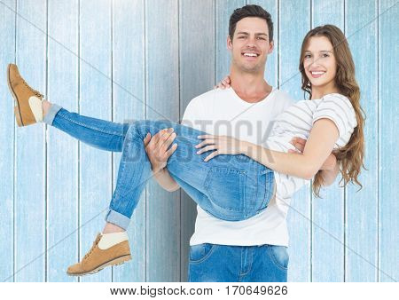 Portrait of happy man carrying his woman against blue wooden background