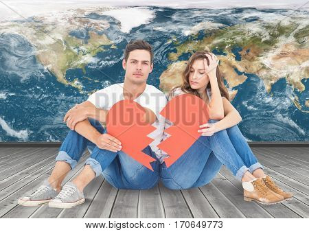 Composite image of couple holding a broken heart against world map background