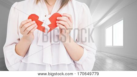 Mid section of woman holding a broken heart in an empty room