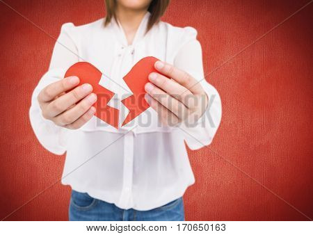 Mid section of woman holding a broken heart against red background