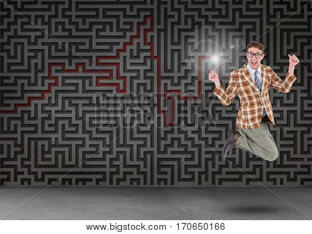 Excited businessman jumping in front of digitally generated maze wall